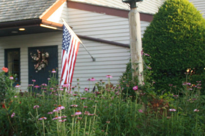white siding trimmed in tan restaurant with red,white, blue American flag at door and surrounded by pink perennial flowers
