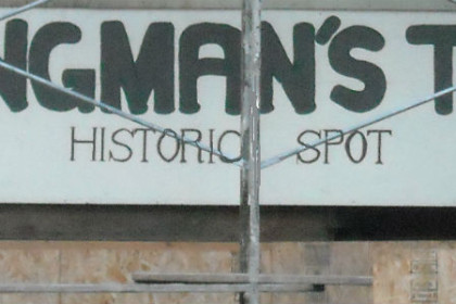 Rectangle sign with white background and black letters reading Hangman's Tree Historic Spot.