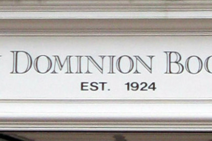 White sign with grey letters reading New Dominion Bookshop, Established 1924