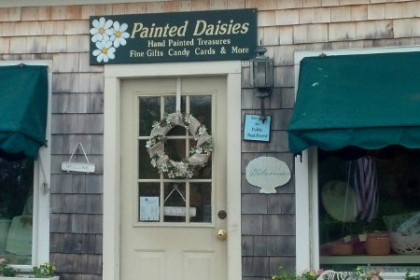 "gray weather shingled building with green awnings over glass windows and a sign above the door reading""Painted Daisies"""