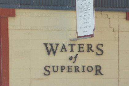 2 front windows of building with Waters of Superior sign in between them