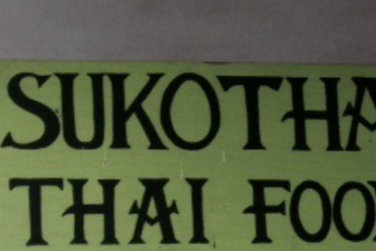 Green sign hanging from ceiling that reads, Sukothai Thai Food
