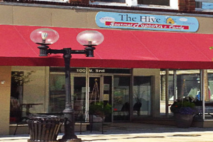 Red awning over beige colored storefront and blue sign above awning that says The Hive