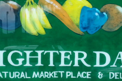 Green background with white lettering Brighter Day Natural Market Place & Deli with painted mixed fruit