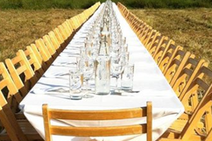 A long table set in a field with wooden chairs and white linens
