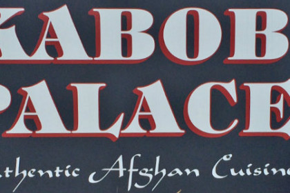 Black sign with white letters spelling Kabob Palace