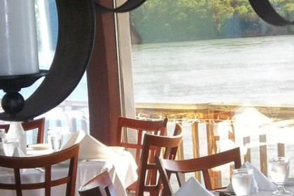 Restaurant tables set with white linen placed in front of a plate glass window with a view of the Niagara River