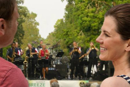 A man and woman smiling at each other as they listen to a band on stage in the background