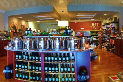 interior of store with shelves filled with glass bottles of olive oil and sign on wall readig Olive Oils Balsamic Vinaigrettes