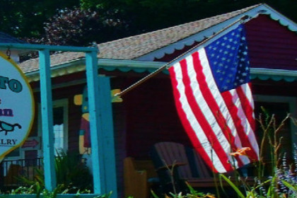 Outside of Pajarito with round sign and American flag