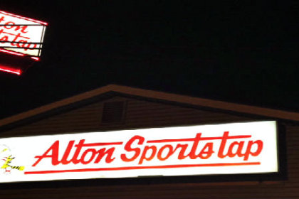 white illumated sign with red letters reading Alton Sports Tap with a dark night sky