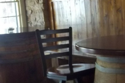 chairs around a barrel table set in front of a window to the street. Candle on table top