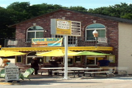 Outside view of The Whole Scoop ice cream shop, outdoor patio with yellow umbrellas