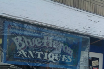 Building facade with blue stained glass sign that reads Blue Heron Antiques