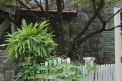 Front of Landis Valley with white picket fence and hanging green ferns