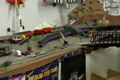 picture of a model train layout with trax, trains, mountain, buildings, bridges and all the small detail that makes up a small town and railroad scene