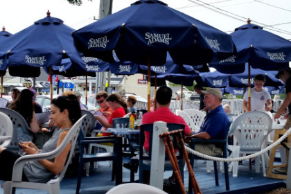 Large blue umbrellas and people sitting at tables on a patio.