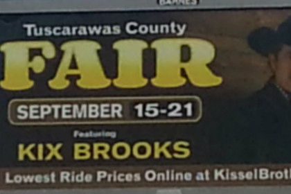 Photo of Tuscarawas County fair billboard with big yellow lettering and a photograph of Kix Brooks