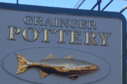 White sign with Grainger Pottery in gold lettering above a gold 3 dimensional fish