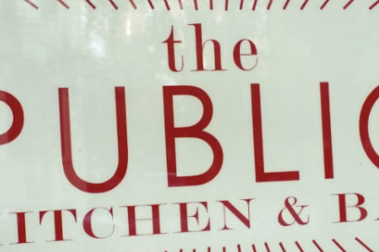 White sign with the Public Kitchen & Bar in red letters and red lines around the lettering, red cirlces around the lines with red and white stripe border.