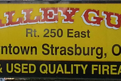 photo of the Valley Gun Billboard. Large bright yellow sign with black and red lettering.