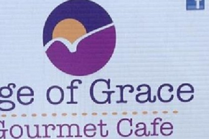 White sign with purple and yellow logo reading Age of Grace Gourmet Cafe
