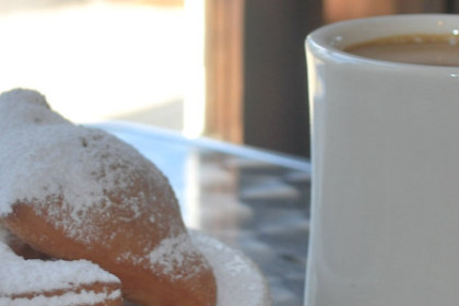 white plate filled with beignets covered in powdered sugar and a white cup filled with coffee