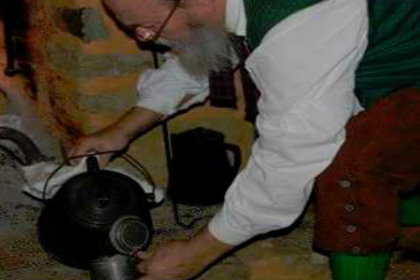 Man with colonial clothing pouring a drink from a kettle in front of a fire