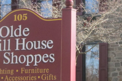 Cranberry colored sign with name of shop in white letters posted in front of sandstone house