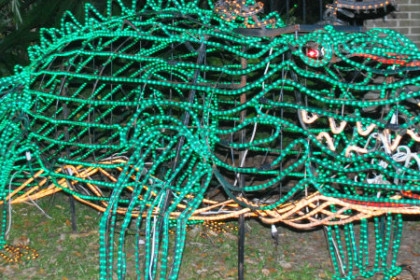Wire framed gator outlined in green twinkle lights.