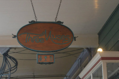 Wooden sign hanging under porch eve from chain reading 3 Muses