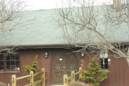 Front view of the Benmarl Winery with brown siding and a green roof.