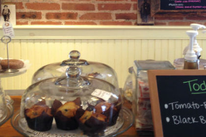 A variety of muffins, donuts and baked goods in glass covered cake plates set on a butcher block counter with an exposed brick and bead board wall in the background behind the counter.