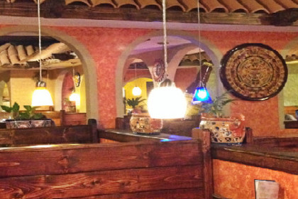 brightly lit restaurant interior with low handing lights, booths, and arched openings between rooms