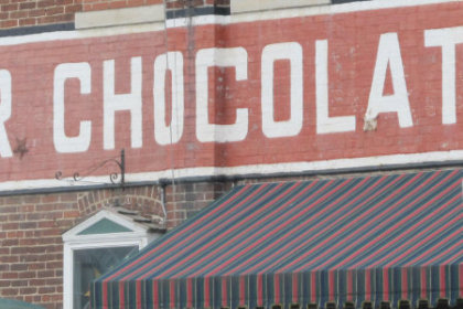 Wilbur Chocolate written in White against a red colored background banner painted on the brick front of the factory building