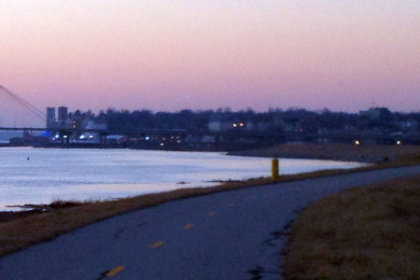wide river confluence with bridge in the distance at dusk