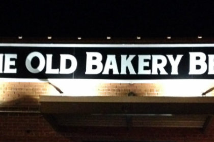 store front sign lit at night and reads The Old Bakery Beer Co.