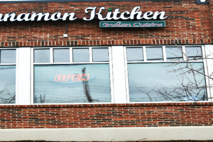 low rise red brick building with reflective widows and sign reading Cinnamon Kitchen