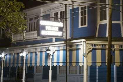2 story New Orleans style structure painted blue with white trim and brightly lit sign reading Commander's Palace