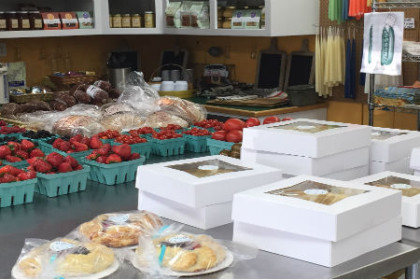 Stainless steel tables with assorted fresh berries in containers, freshly wrapped pies and jams on shelf in the background