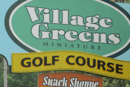 Village Greens spelled in white on a green sign/with golf course spelled in black on a yellow banner.