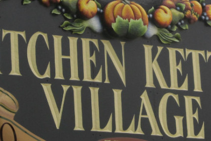 Kitchen Kettle Village spelled out in gold on a dark green background sign.