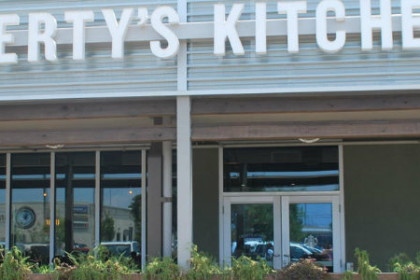 Glass store front with big bold letters spelling Liberty Kitchen
