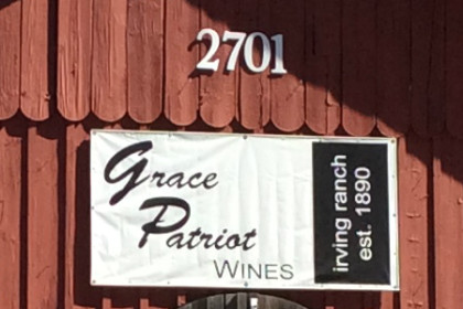 Red wood barn with sign reading Grace Patriot Wines