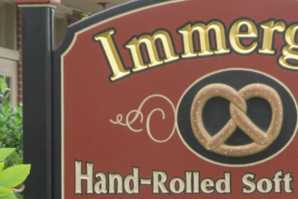 Sign with Immergut hand-rolled soft pretzels carved in gold on a red sign outside the shop.