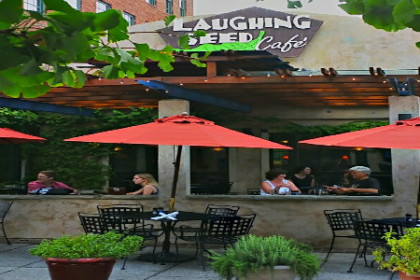 Light gray building with quasi Spanish appearance, green potted plants outside. Outside seating with wide red umbrellas.