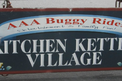 Blue sign with white letters reading Kitchen Kettle Village AAA Buggy Rides