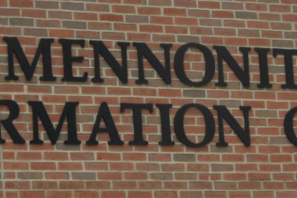 Mennonite Information Center in black letters against a red brick wall.
