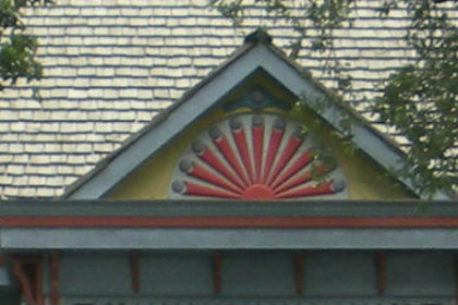 Roof line and peak of plantation home with decorative carved fan in teals and reds