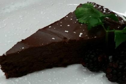 Shiny, white round dessert plate with slice of chocolate pie and green garnish